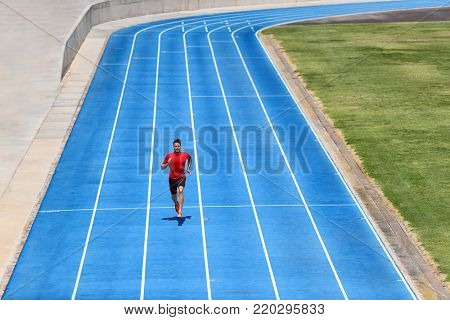 Sprinter runner athlete man sprinting on outdoor track and field running lanes at stadium. Sport and health active training on blue tracks. poster