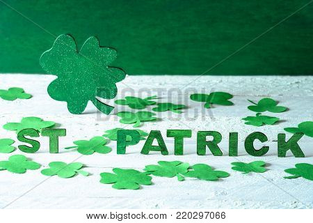 Big shamrock and the words St Patrick - Saint Patrick words spelled with green wooden letters and a big green shamrock in the back, surrounded by paper clovers, on a wooden background.