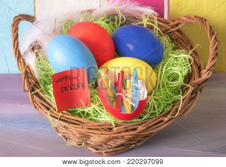 Easter basket and eggshell with rolled messages - Wicker basket full with painted eggs and an eggshell with rolled paper notes and one with the words happy easter, on a colorful wooden background.