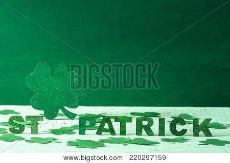 St Patrick words and green shamrock - The words St Patrick written in green wooden letters and a big green clover in the back, surrounded by paper shamrocks, on a green wooden background.