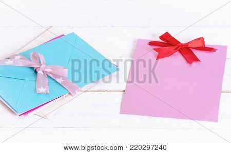 Pile of envelopes and cute message card - Bunch of multicolored letters tied together with pink ribbon and bow near a blank pink paper note with a red bow, on a white wooden background.