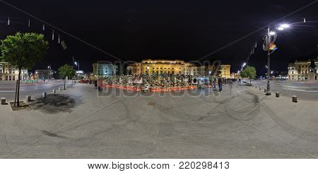 BUCHAREST, ROMANIA - DECEMBER 16, 2017: 360 Panorama of Piata Revolutiei at nighttime with heaps of flowers, candles and leaflets put in front of the Royal Palace in rememberance of the deceased king, Michael I.