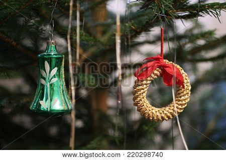close photo of a twig of Christmas tree decorated with green bell and straw ring