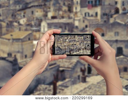 Female taking picture of old town Matera in Italy on mobile phone. Landscape of the Matera old town on smart phone. (sassi di Matera)