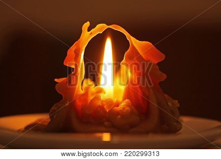 weirdly shaped melting candle burning with bright flame in the darkness