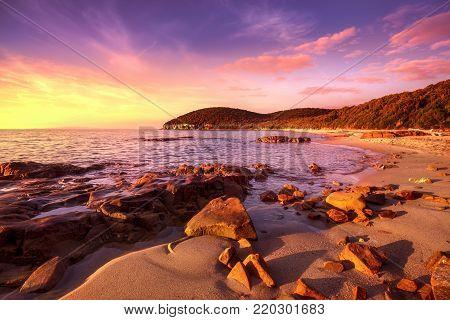 Sunset Cala Violina bay beach in Maremma, Tuscany. Travel destination in Mediterranean sea. Italy, Europe.