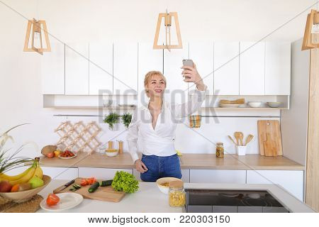 Marvelous girl housewife with smartphone communicates by video call with husband and greets with hand, with smile on face shows what she preparing for dinner and directs camera to cucumbers and tomatoes with lettuce, pasta and fruit in bowl,