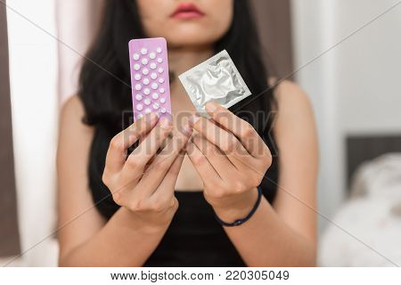 Asian woman holding condom and birth control pills in the bed room., Health and medical concept