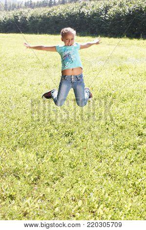 Little girl. Bounce. Juicy green grass. Child