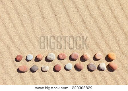 Pattern of colored pebbles on clean sand. The concept of peace and contemplation. Flat lay, top view. Zen background, harmony and meditation concept