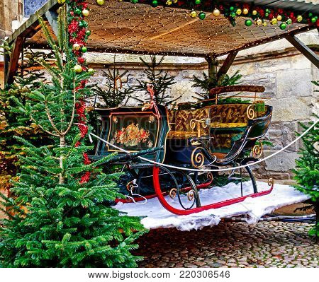 MUENSTER WESTPHALIA, GERMANY-DECEMBER 15, 2017: Artistically decorated old sleigh at the Christmas market against the historic walls of St. Paul's Cathedral