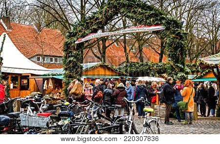 MUENSTER WESTPHALIA, GERMANY-DECEMBER 15, 2017: Small Christmas Market set against the historic walls of the Ueberwasserkirche is one of five distinct markets scattered across the Altstadt with a wide selection of crafts and special delicacies