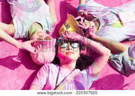 Chengdu, China - July 2, 2016 : Three girls covered by purple color powder lying down on the ground for the Chengdu Color Run