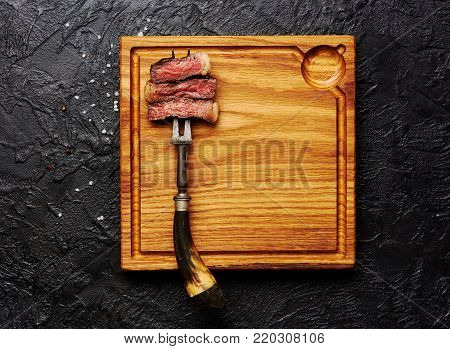 Slices of medium rare grilled Steak on meat fork on wooden meat cutting board. Black concrete background. Copy space. Top view.