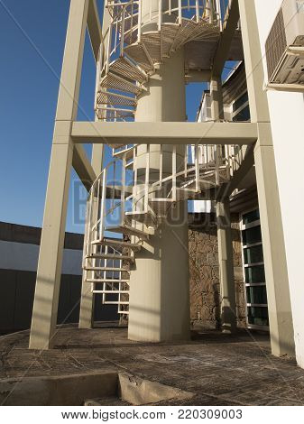 A steel spiral staircase, outdoors with blue sky background