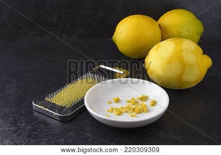 organic lemon fruit, freshly grated peel or rind and the metal grater on a dark slate background with copy space, selected focus, narrow depth of field