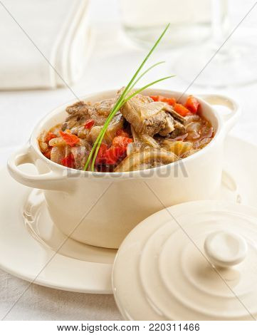 Lamb stew with onions and bell pepper in a ceramic cooking pot.