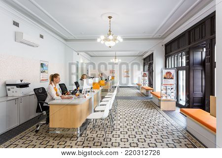 Grodno, Belarus - August 7, 2017: Cashiers Managers In A Modern Bank In The Workplace In White Loft