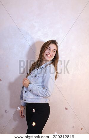Cute young woman smiles beautifully and in high spirits looks and poses, changing poses to camera in bright silvery confetti, dancing and  standing against background of light wall in room.  European woman with fair-haired hair dressed in striped T-shirt