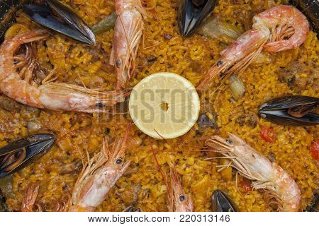 Top view of a typical spanish food, a paella Valenciana with rice, fish and vegetables