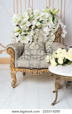 Luxurious vintage interior in the aristocratic style with elegant armchair and flowers. Retro, classics