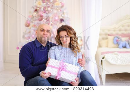 Beautiful spouses, loving husband and wife smile and look at camera, posing and hugging each other, sitting on floor in bright bedroom decorated in festive mood on background of large bed and Christmas tree. Woman of European appearance with long curly bl
