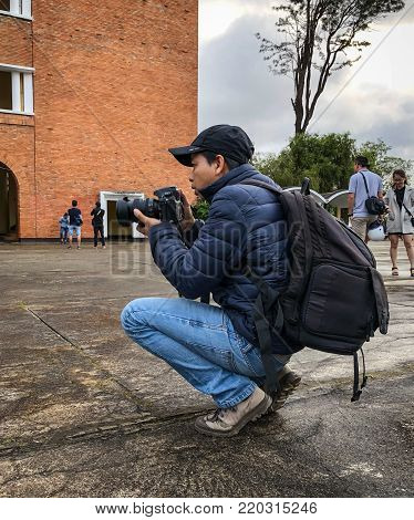 Dalat, Vietnam - Dec 3, 2017. A photographer taking images at Lycee Yersin School in Dalat, Vietnam. Da Lat was developed as a resort by the French in the early 1900s.