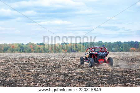 Quad bike was taken from behind. Red buggy in a plowed field against the background of autumn trees. concept of power speed and freedom.