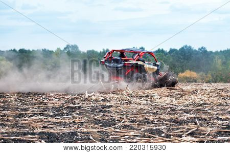 Red buggy rushes through the field in the dust. The concept of speed of power and freedom.