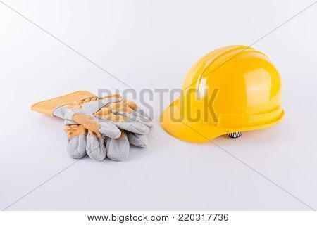 Yellow safety helmet and Safety gloves on white background. Hard hat and thick gloves on white isolated background. Safety equipment concept. Worker and Industrial theme.