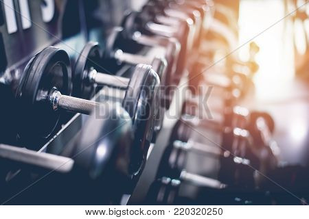 Black Steel Dumbbell Set. Close Up Of Dumbbells On Rack In Sport Fitness Center. Workout Training An