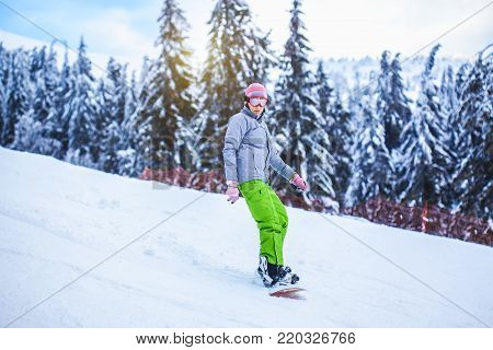 woman snowboarder riding in the picturesque mountains between the Christmas trees