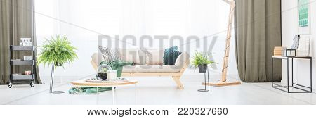 Beige sofa with decorative cushions standing next to the window in bright, natural living room interior