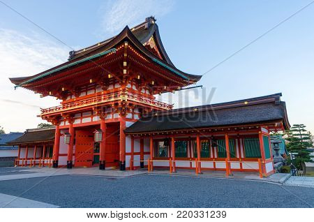 red beautiful buddhist temple building at Fushimi Inari Shrine is the famous tourist attraction temple in Kyoto, Japan with bright blue sky at the moring in autumn
