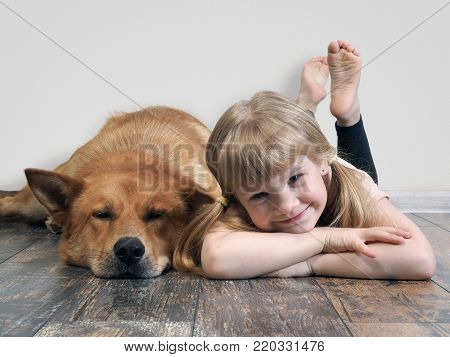 happy child and a huge dog. Girl and dog lying on the floor