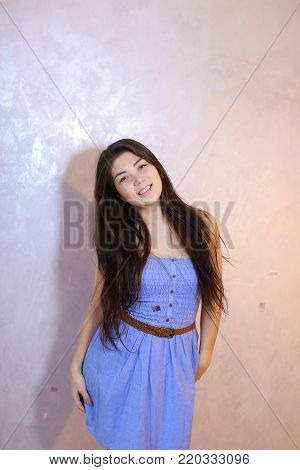 Cute young woman smiles beautifully and in high spirits looks and poses, changing poses to camera in bright silvery confetti, standing against background of light wall in room. Dark-haired woman dressed in blue dress. Concept of beautiful and happy girl,