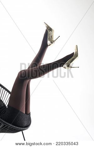 Tights. . Female legs in pantyhose and golden high heels