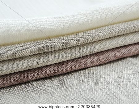 Pile of handmade dull-colored waffle linen cotton napkins towels on white linen background. Different colors. Food photo props. Natural waffle linen cotton fabric.