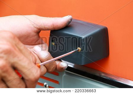 Man mounting the plastic handle protection to the body of fire truck. Man fixed handle by using screwdriver. Worker background concept.