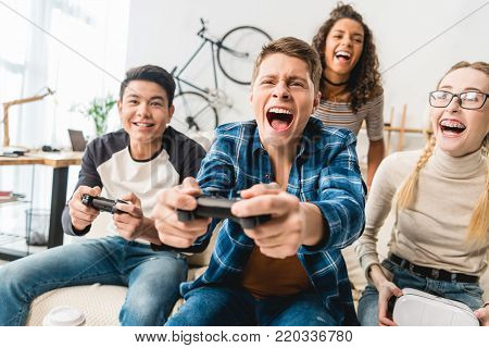 view of laughing multicultural teens playing video game