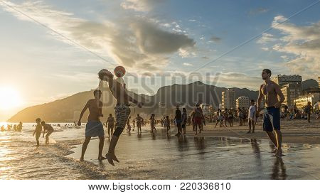 Rio de Janeiro, Brazil - Jan 1st, 2018: Young men play Keepy-Uppy in Portuguese altinho on the beach in Ipanema, Rio de Janeiro, Brazil at sunset