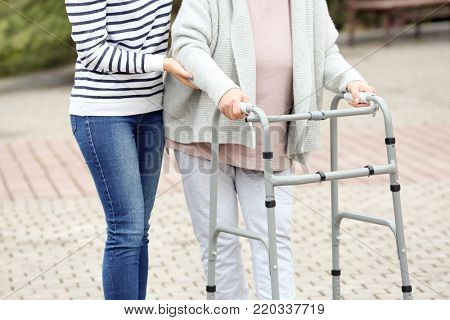 Young woman and her elderly grandmother with walking frame outdoors