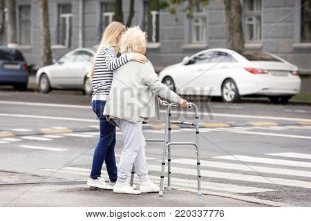Young woman helping her elderly grandmother with walking frame to cross the road
