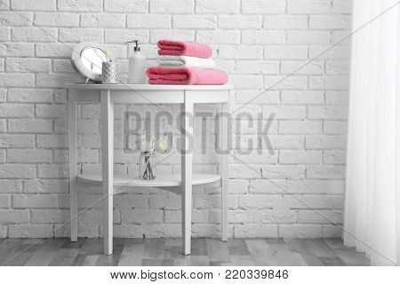 Table with clean towels and toiletries near white brick wall