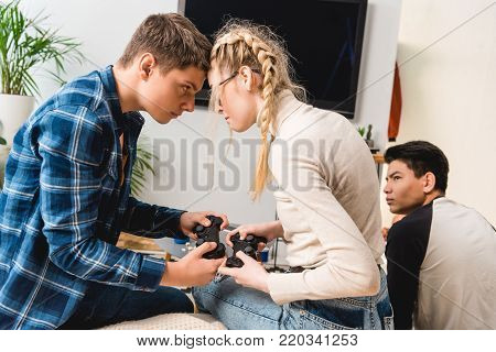 boy and girl aggressively touching with foreheads while playing video game