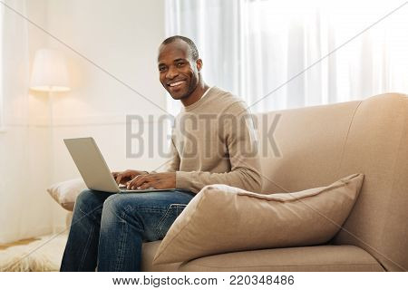 In high spirits. Content dark-eyed afro-american man grinning and working on the computer while sitting on the couch and a lamp and a carpet in the background
