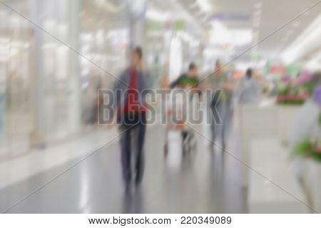 Abstract defocused motion blurred people walking in shopping center, supermarket. Unrecognizable figures, urban lifestyle concept. For background , backdrop, substrate, composition use