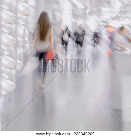 Abstract defocused motion blurred young people walking in the shopping center. Beautiful figure of a girl with shopping bags close-up, background.