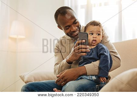Fatherhood. Cheerful dark-haired afro-american man smiling and showing something on the phone to his son while the child sitting on his lap