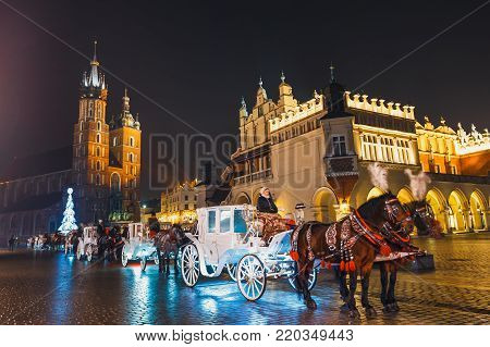 Krakow, Poland - January 22, 2017: Horse-drawn Carriage before the Sukiennice on The Main Market Square in Krakow, night view, Poland
